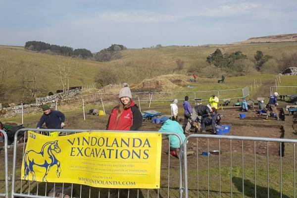 2018 Excavations Banner stretching across the new excavation area. Volunteers working in background